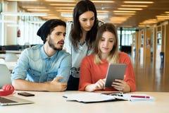University students using digital tablet in university library. University students sitting together at table using digital tablet. Group study in university stock photo
