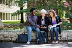 University Students Using Digital Tablet. Professor helping students on campus using digital tablet Stock Photo