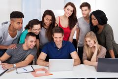 University students using laptop together. Group of multiethnic university students using laptop together in classroom Stock Photography