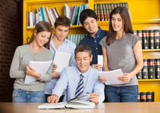 University Teacher With Books Explaining Students Stock Photo