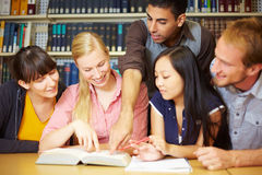 University training. Group of students learning in library at university stock photo