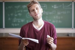 University young male professor teaching students in university holding notebook with chalk. University young male professor teaching students in university Royalty Free Stock Photos