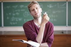 University young male professor teaching students in university holding notebook with chalk stock image