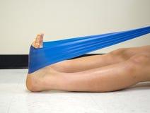 Uniwerek atleta używa theraband ćwiczenia zespołu umacniać jej kostkę zdjęcia royalty free
