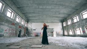 Unkempt hall with a female violinist playing the instrument. 4K stock video
