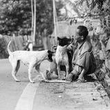 Unknow-Dorfbewohnerspiel und küssen seinen Hund während er arbeitend stockfotos