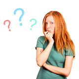 Unknowing. Thinking red-haired girl isolated on a white, questions marks at background Stock Photography