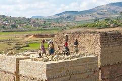 Unknown Africans working hard in brickyard - Madagascar. ANTSIRABE, MADAGASCAR, SEPTEMBER 13, 2014: Unknown Africans working hard in brickyard - Madagascar royalty free stock image