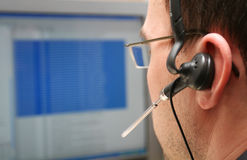 Unknown analyst. A male analyst working at a computer, with a headset, shot from behind focus on headset Royalty Free Stock Photo