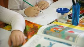 Unknown boy and girl in class draw paints in an stock video