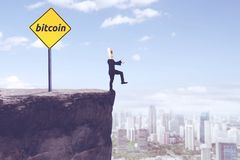 Unknown businessman with bitcoin word on cliff. Picture of unknown businessman with cardboard head walking on the cliff with bitcoin word on a signpost Stock Photography