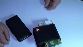 Unknown businessman pulls, lays down the money in the purse. stock footage