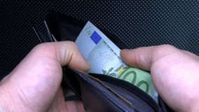 Unknown businessman pulls, lays down the money in the purse. stock video footage