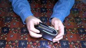 Unknown businessman pulls, lays down the money in the purse. HD stock video footage