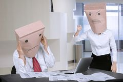 Unknown businesswoman scolding her employee in office. Unknown businesswoman with a paper bag on his head, scolding her anonymous employee in the office Royalty Free Stock Images