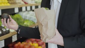 Unknown Caucasian man in suit putting pomelo into paper shopping pack and leaving. Unrecognizable guy buying tasty