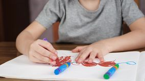 Unknown child drawing with bright colored pencils on white paper while sitting at the table. The concept of development stock video