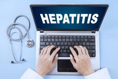 Unknown doctor with hepatitis word and laptop. High angle view of unknown male doctor hand using a laptop with hepatitis word on the laptop screen Royalty Free Stock Photo