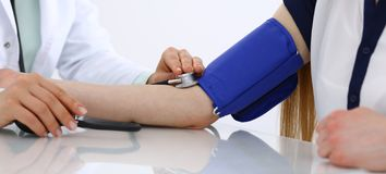 Unknown doctor woman checking blood pressure of female patient, close-up. Cardiology in medicine and health care concept royalty free stock photos
