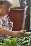 Unknown elderly woman buys cucumbers at the market Stock Photo