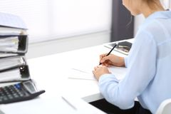 Unknown female bookkeeper or financial inspector calculating or checking balance, making report, close-up. Internal. Revenue Service at work with financial royalty free stock photo