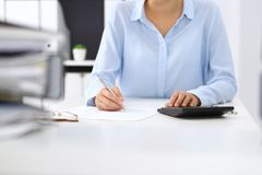 Unknown female bookkeeper or financial inspector calculating or checking balance, making report, close-up. Internal. Revenue Service at work with financial stock images