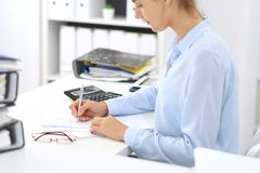 Unknown female bookkeeper or financial inspector calculating or checking balance, making report, close-up. Internal. Revenue Service at work with financial stock photo