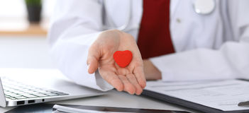 Unknown female doctor with stethoscope holding heart Stock Image