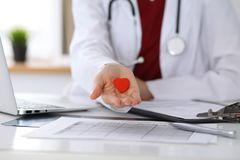 Unknown female doctor with stethoscope holding heart. Children`s cardiology and medical care, stop abortation concept stock photos