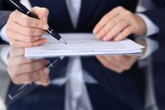 Unknown female hands with pen over document of contract. Agreement signing or business concept.  stock photos
