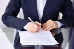 Unknown female hands with pen over document of contract. Agreement signing or business concept.  stock images