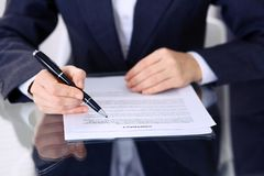 Unknown female hands with pen over document of contract. Agreement signing or business concept.  stock photography
