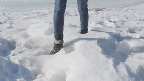 Unknown female in jeans and trekking winter shoes walking in deep snow stock video