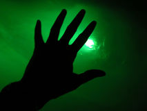 Unknown Future. Sillouette of a hand reaching into the light Stock Photos
