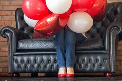 Unknown girl hidden in red and white helium balloons on sofa. Colorful balloons and women legs in red shoes. Birthday decoration.
