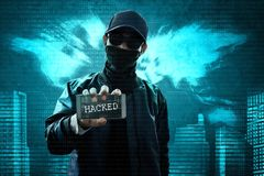 Anonymous hacker holding mobile phone. Unknown hacker holding mobile phone Royalty Free Stock Image