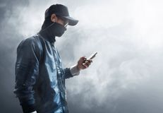 Anonymous hacker using mobile phone. Unknown hacker using mobile phone Stock Images