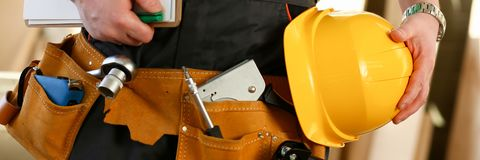 Unknown handyman with hands on waist and tool belt with construction tools against grey background. DIY tools and manual. Handyman with hands on waist and tool stock photo