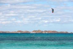 Unknown kitesurfer surfing on a flat azure water of Atlantic ocean in Corralejo Royalty Free Stock Photography