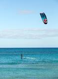 Unknown kitesurfer surfing on a flat azure water of Atlantic ocean in Corralejo Royalty Free Stock Photos