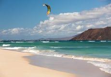 Unknown kitesurfer surfing on a flat azure water of Atlantic ocean in Corralejo, Fuerteventura Royalty Free Stock Photography