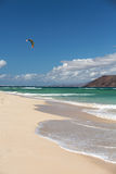 Unknown kitesurfer surfing on a flat azure water of Atlantic ocean in Corralejo, Fuerteventura Royalty Free Stock Photo