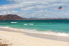 Unknown kitesurfer surfing on a flat azure water of Atlantic ocean in Corralejo, Fuerteventura, Royalty Free Stock Photos