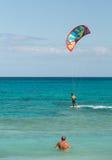 Unknown kitesurfer surfing on a flat azure water of Atlantic ocean in Corralejo, Fuerteventura, Stock Image
