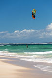 Unknown kitesurfer surfing on a flat azure water of Atlantic ocean in Corralejo, Fuerteventura Royalty Free Stock Image