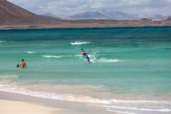 Unknown kitesurfer surfing on a flat azure water of Atlantic ocean in Corralejo, Fuerteventura Royalty Free Stock Photos