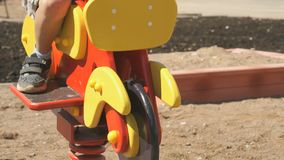 Little boy ride horse - swing outdoors stock video