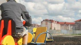 Little boy ride horse - swing outdoors stock video footage