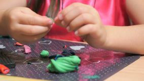 Little girl sculpting figures from plasticine. Unknown little girl sitting at the desk sculpts a different figures from made of colored modeling plasticine in stock video footage
