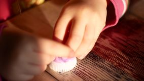 Unknown little girl sitting at the desk sculpts a different figures from made of colored modeling plasticine in the. Nursery stock footage